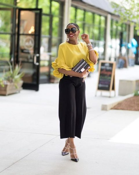 a casual yet outfit with black culottes, a sunny yellow top with ruffled sleeves, black spike shoes and a black clutch