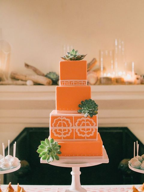 a coral wedding cake with floral and geometric patterns and succulents on a white stand for a 70s wedding