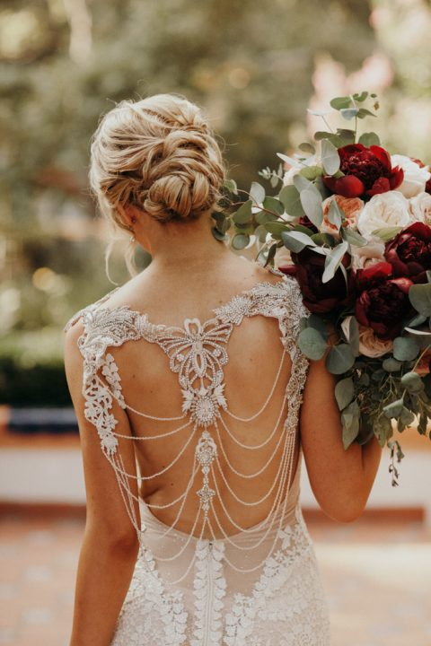 a fantastic lace mermaid wedding dress with a cutout back with chains and embellishments and a train