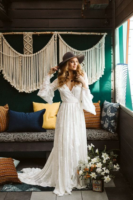 a lace wedding dress with bell sleeves, a train and a grey hat for a boho chic 70s inspired look