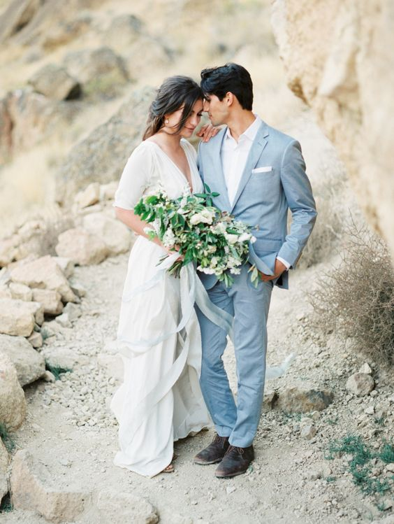 a light blue suit paired with a white shirt is a cool effortlessly chic groom's look for a coastal or beach wedding