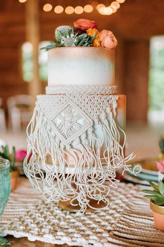 a gradient copper and mint wedding cake topped with fresh blooms and greenery and with macrame hanging