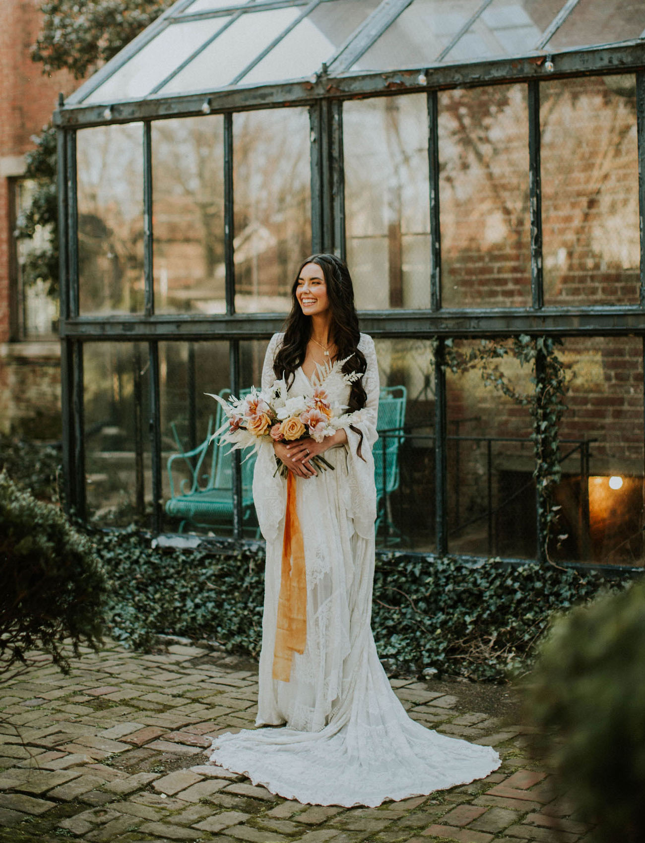 a lace wedding gown with bell sleeves and a V neckline plus a train is a great idea for a 70s boho bridal look