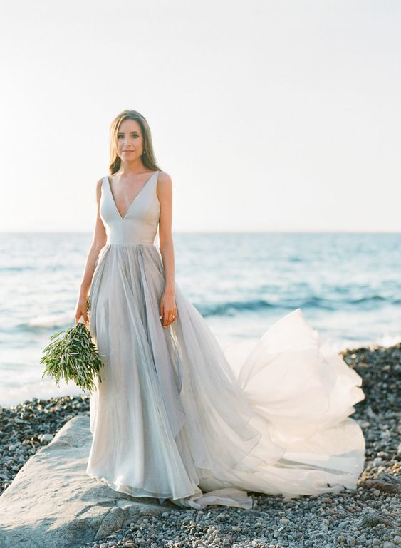 a modern bridal separate of a neutral top with a deep neckline and a layered skirt with a train