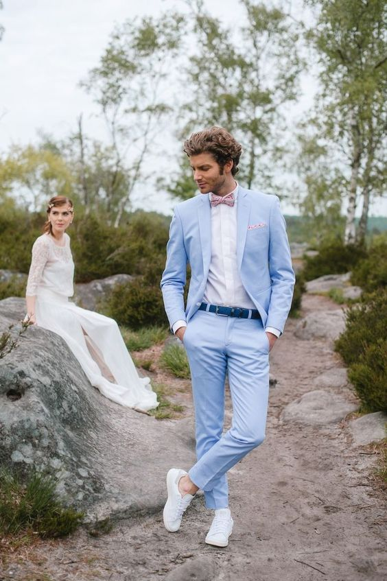 a light blue suit, a bright blue belt, a white shirt and sneakers and a pink printed bow tie