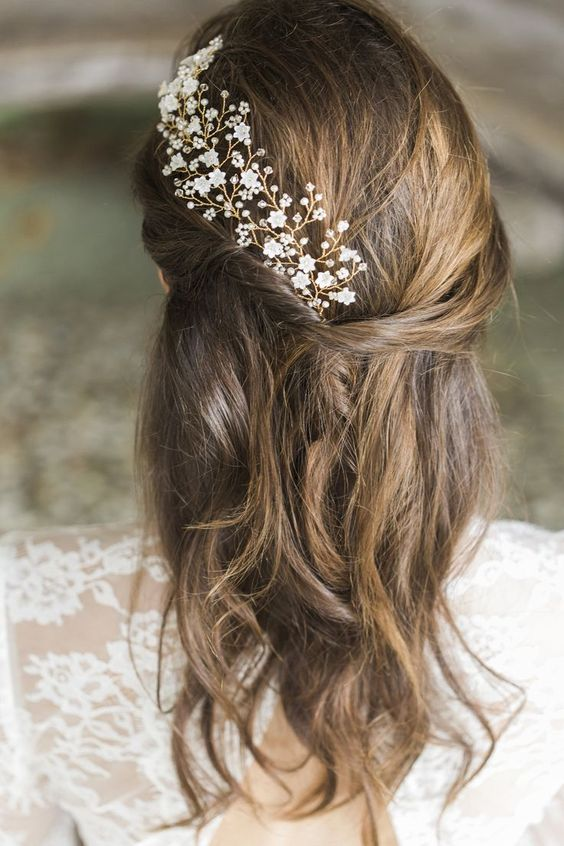 a messy half updo with a floral hair vine, with white and sheer crystals