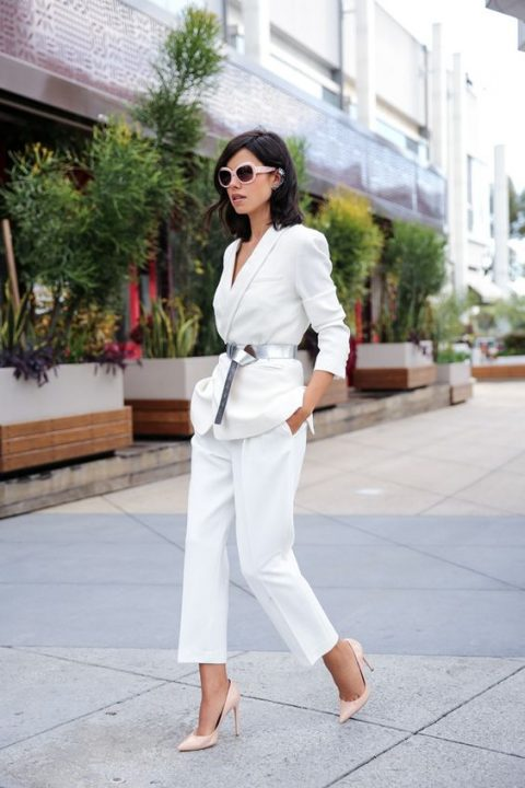a modern white pantsuit with a deep neckline, a metallic belt and blush shoes to feel comfortable