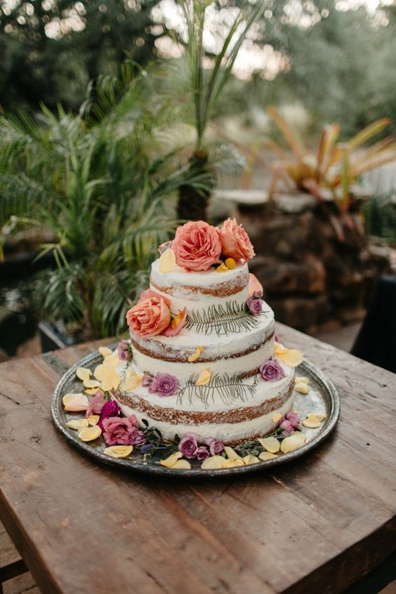 a naked wedding cake decorated with muted colored blooms, greenery and lots of petals