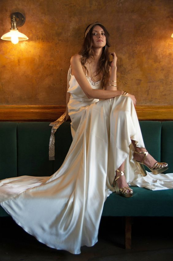 a neutral lace spaghetti strap wedding dress paired with metallic shoes and accessories for a boho look