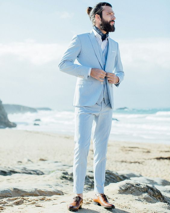 a light blue three-piece suit, a white shirt, a neck tie, brown shoes and a man bun for a coastal groom's look