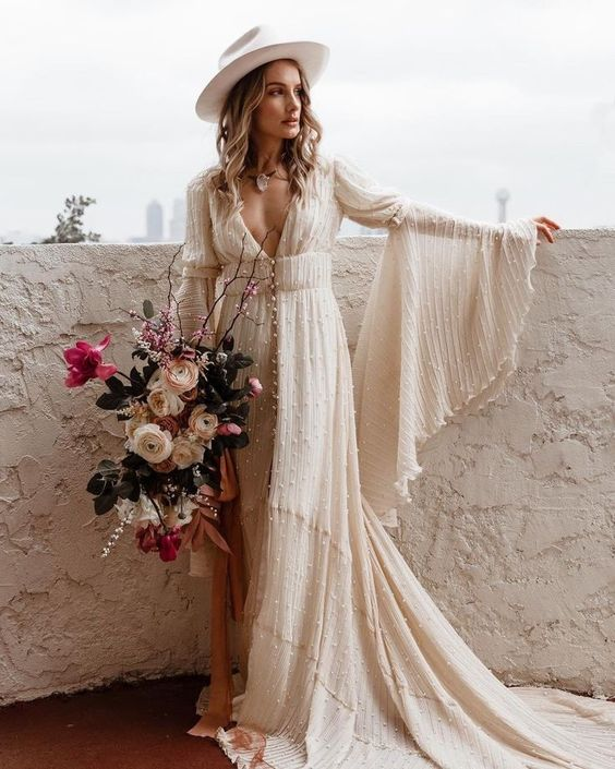 a pearled A-line wedding dress with a deep neckline, bell sleeves, a white hat and a train for a boho look