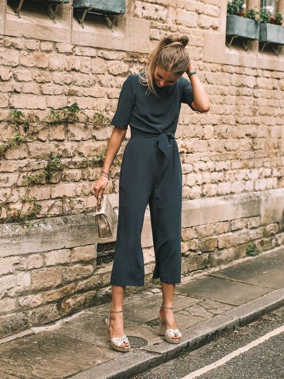a polka dot jumpsuit with cropped pants, short sleeves, neutral platform shoes and a small matching bag