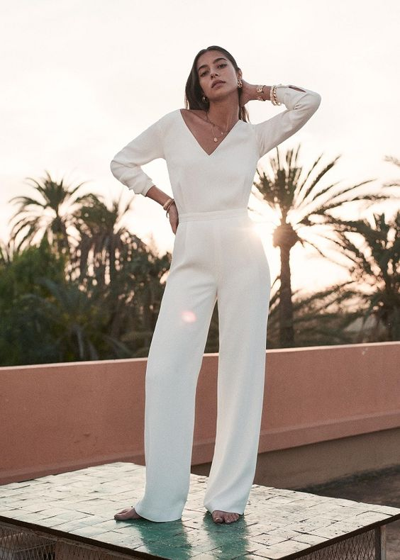 a simple plain white jumpsuit with a deep V-neckline and long sleeves is all you need for a casual wedding