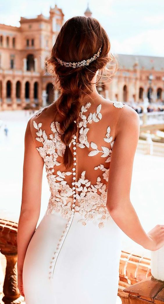 a sleeveless sheath wedding dress with a white floral and botanical applique back and a row of buttons