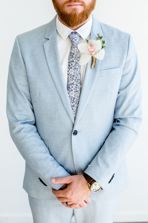 a light blue wedding suit, a white shirt and a blue floral print tie plus an orchid boutonniere for a tropical groom