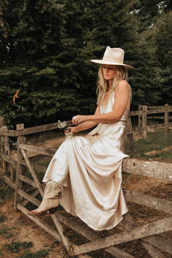 a silk spaghetti strap wedding dress with neutral cowboy boots and a neutral hat for a boho rustic bridal look