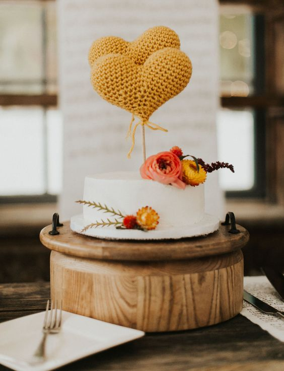 a white wedding cake accented with bold blooms and yellow knit hearts as toppers that brign that 70s feel to the wedding