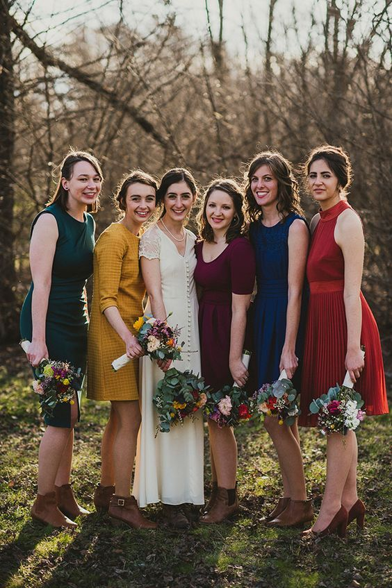 simple mismatching knee dresses in jewel tones and brown booties will make up a bold look for a fall wedding