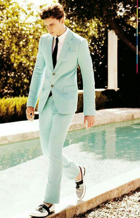 a mint green suit with a white shirt and a black tie and retro inspired black and white moccasins for a spring groom