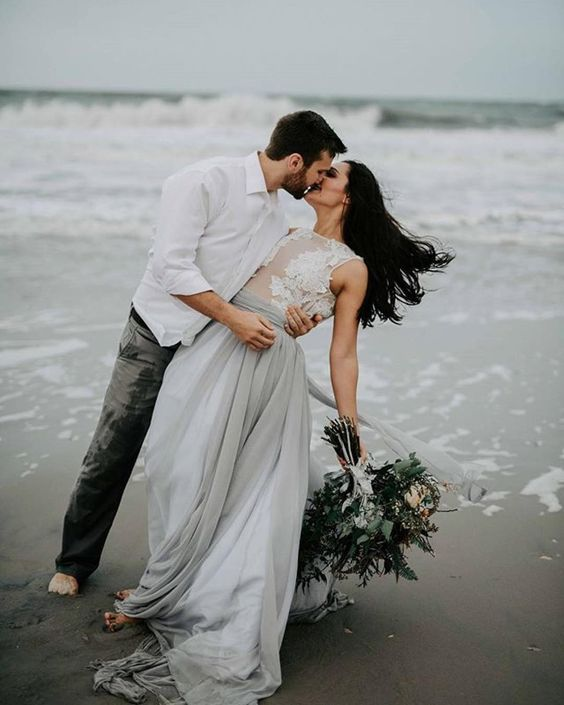 a sexy and romantic bridal separate of a white lace sleeveless top and a grey layered skirt with a train for a coastal bride