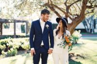 25 a white pantsuit, black strappy shoes and a matching hat for a casual yet bold bridal look
