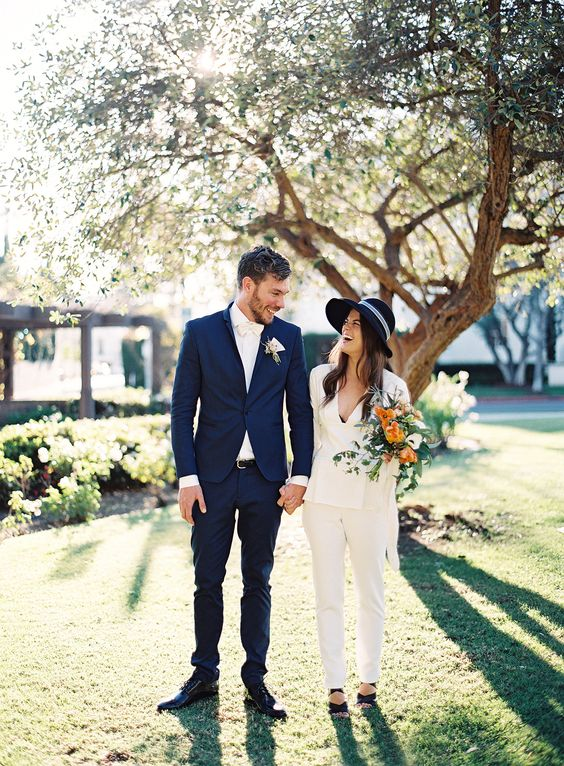 a white pantsuit, black strappy shoes and a matching hat for a casual yet bold bridal look