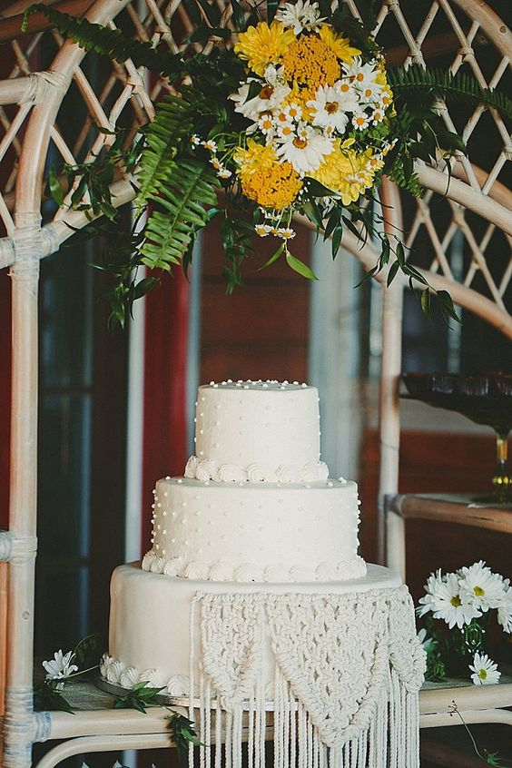 a white wedding cake decorated with macrame is very boho and hippie-like, which is great for a 70s wedding
