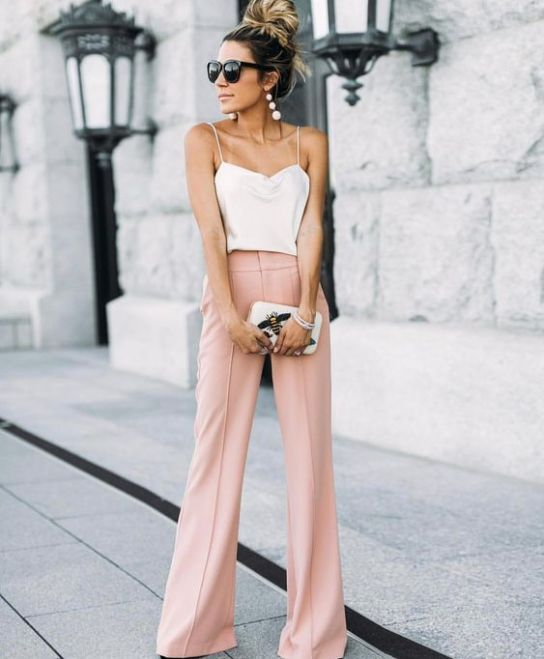 pink wideleg pants, a creamy spaghetti strap top, statement earrings, a small clutch with appliques for a casual summer wedding