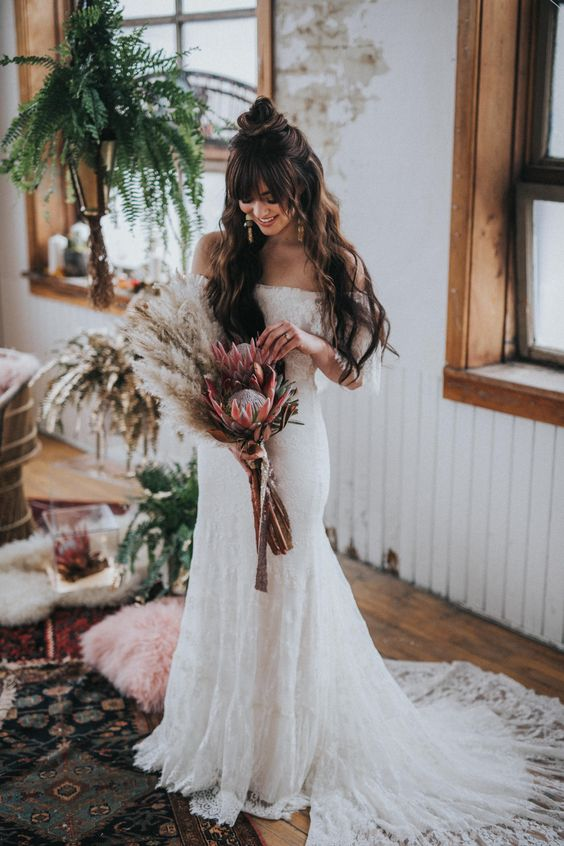 an off the shoulder lace mermaid wedding dress with a long train for a boho chic wedding look