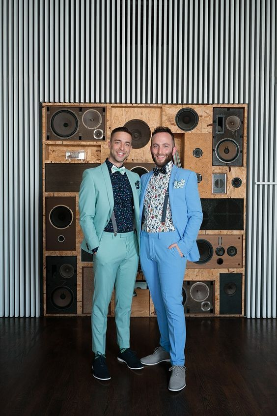 pastel grooms' looks with a green and blue suit, floral shirts, suspenders, bow ties and sneakers for a colorful wedding