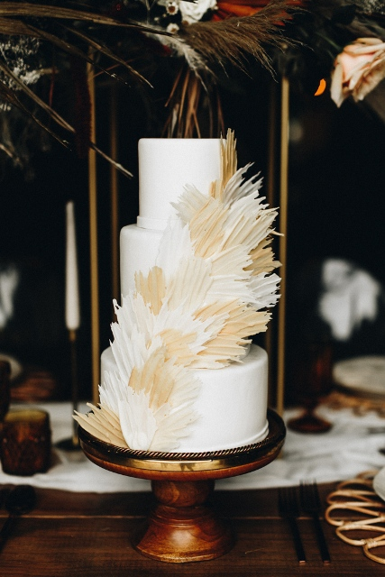 A simple white three tiered cake with beige and light brown feathers one the wooden stand