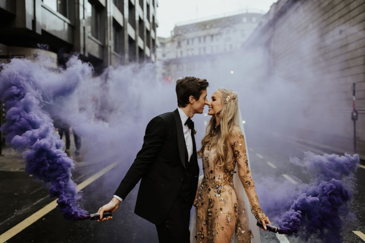 a beautiful wedding portrait with purple smoke bombs create an impression that there's nobody else here