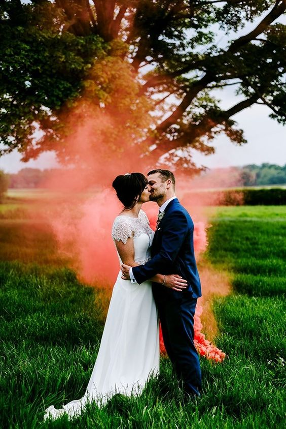 bright coral smoke highlighting the couple and creatign an ambience in the space