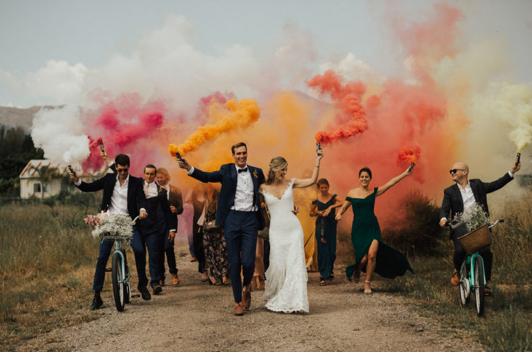everyone rocking colorful smoke bombs as a creative idea for a wedding exit