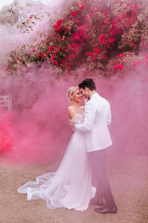highlight the color and the mood with colorful smoke bombs like here - pink smoke and fuchsia blooms