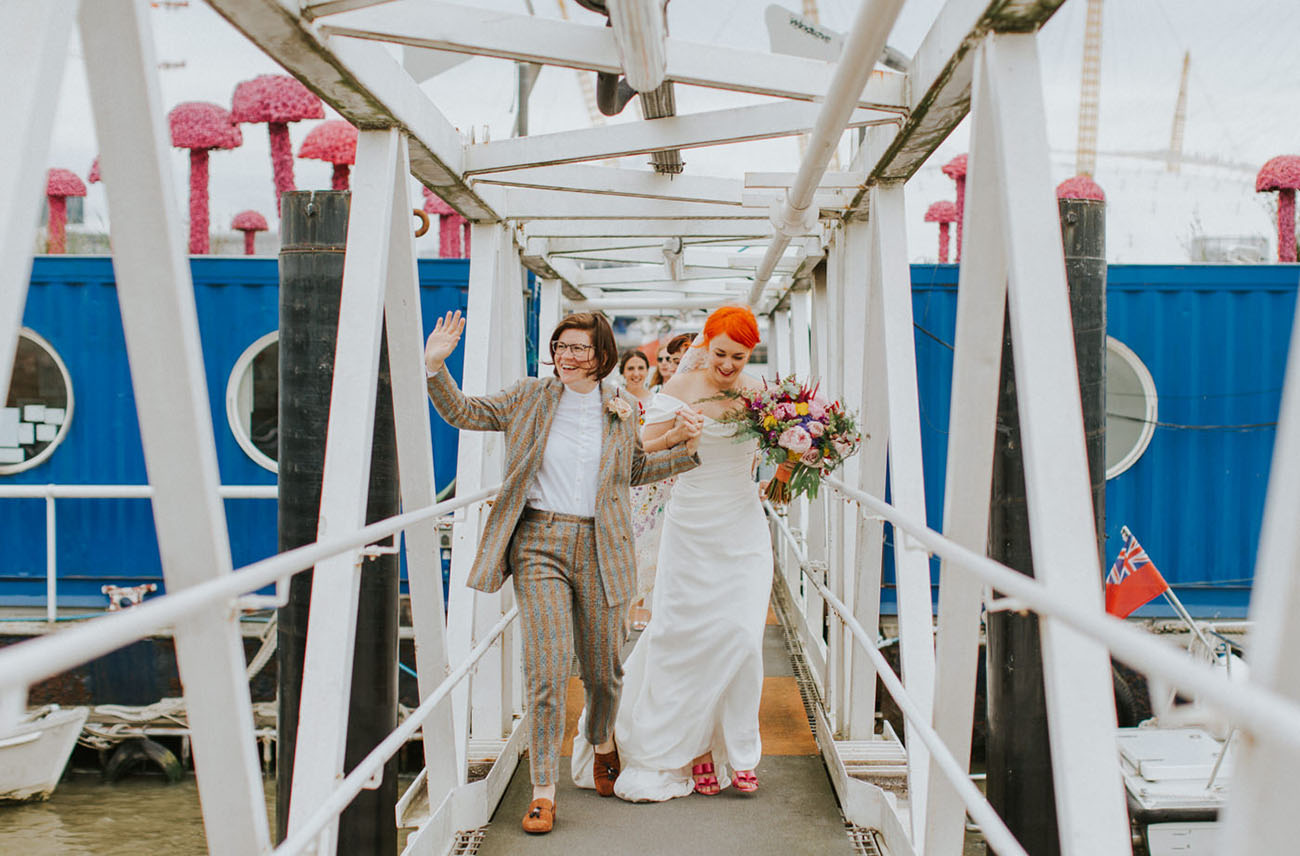 One bride was rocking a colorful striped suit, a white shirt and rust colored loafers, the second girl was wearing an off the shoulder wedding dress and pink bow shoes