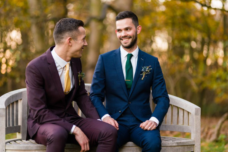 One groom was wearing a three-piece burgundy suit with a yellow tie, and the second was rocking a navy suit with an emerald tie