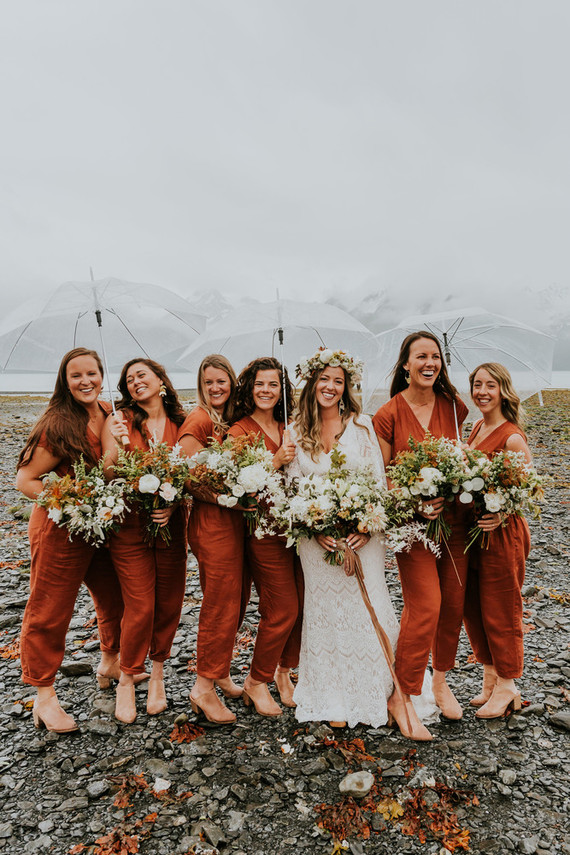 The bride was wearing a boho lace maxi wedding dress with bell sleeves, and the bridesmaids were rocking rust jumpsuits and nude shoes