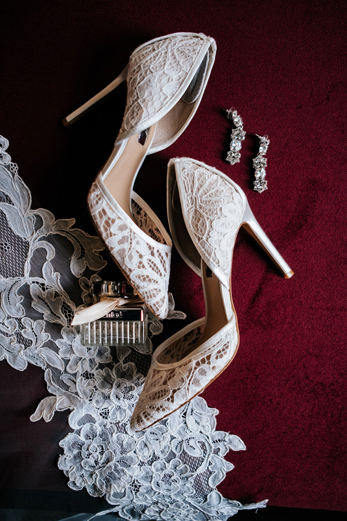 The bride was wearing gorgeous white lace shoes and statement earrings