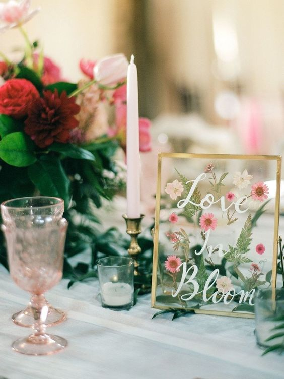 a beautiful wedding sign with pressed pink blooms and greenery is a cool wedding table decor idea