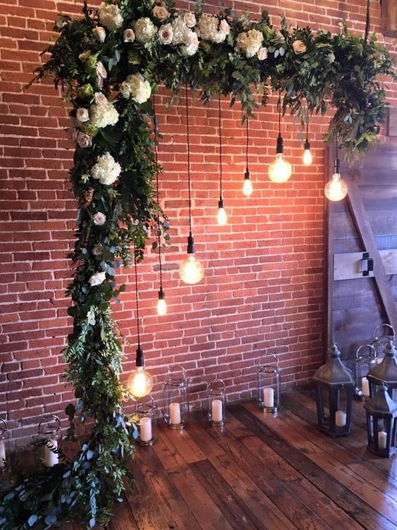an indoor wedding arch done with greenery and neutral and pastel blooms, hanging bulbs and candles in candle lanterns