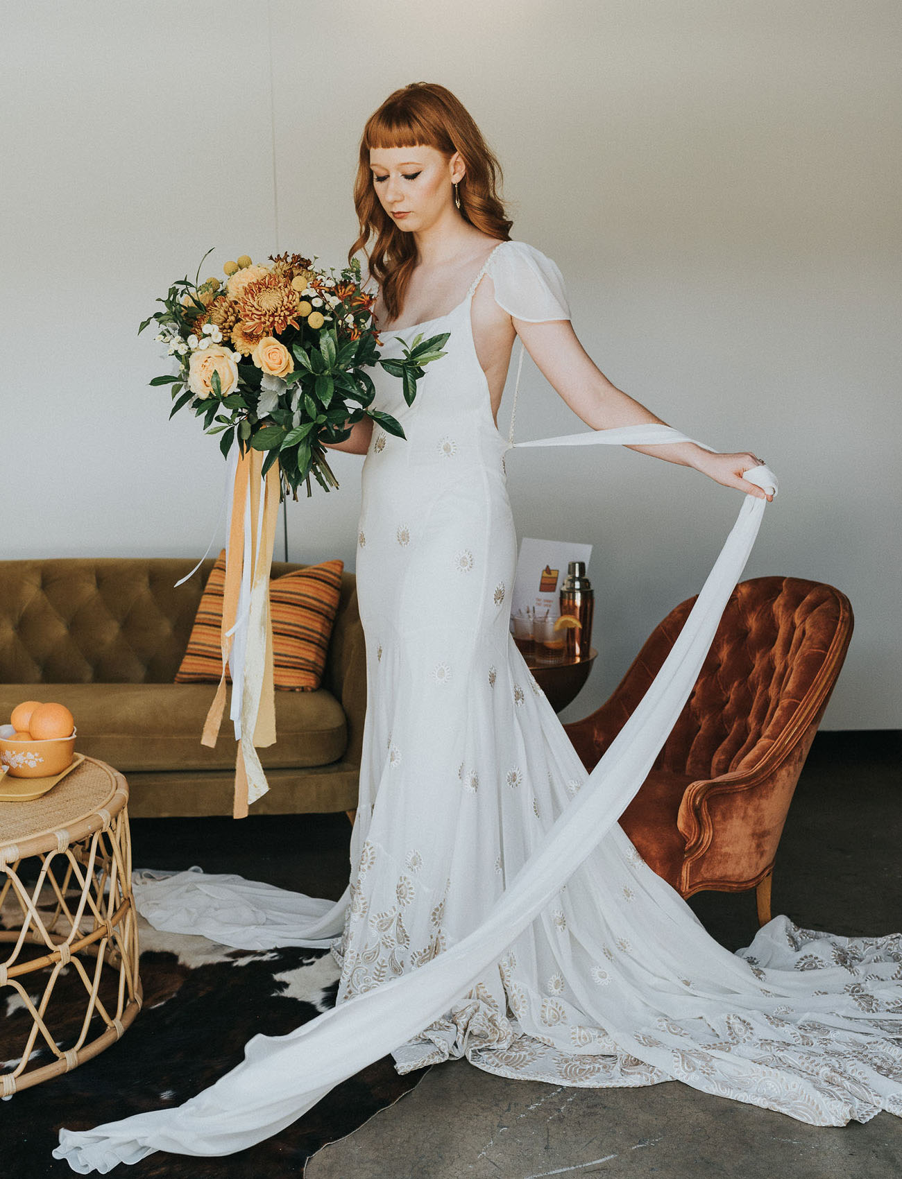 One bride was wearing a chic sheath wedding gown with a train and cap sleeves plus gold embroidery