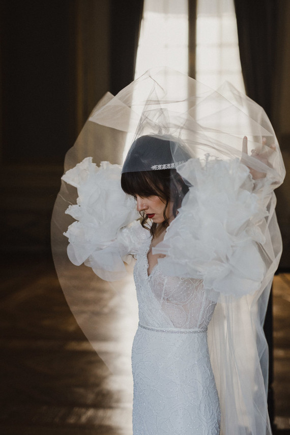 The bride was wearing a sparkling sheath wedding dress with an embellished sash and whimsy ruffled sleeves