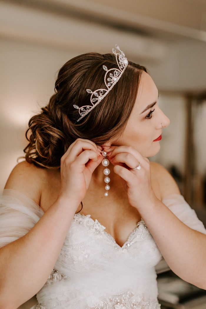 The bride was wearing an off the shoulder wedding dress with an embellished bodice, a crystal crown and statement pearl earrings