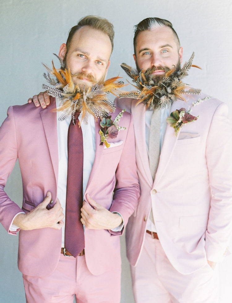 The grooms were rocking light pink suits, with a burgundy and grey tie, and fancy beards styled with feathers