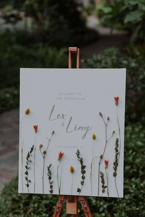 a beautiful wedding sign done with pressed dried blooms and greenery and silver calligraphy looks very chic