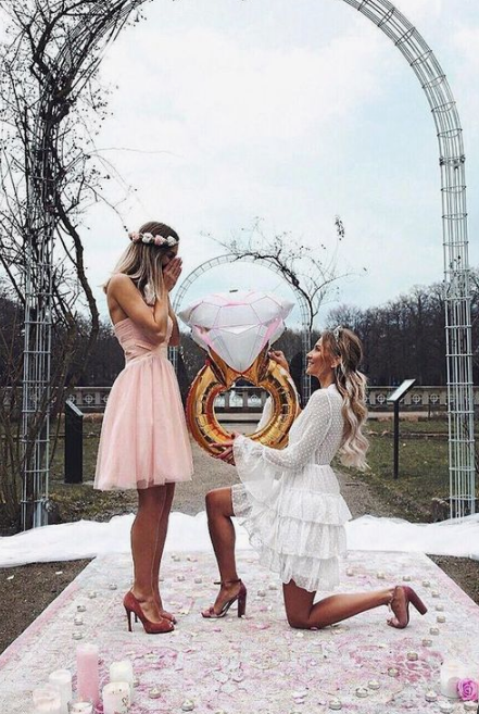 a glam proposal in pink, with candles, crystals and a playful balloon ring is a very cute and fun idea