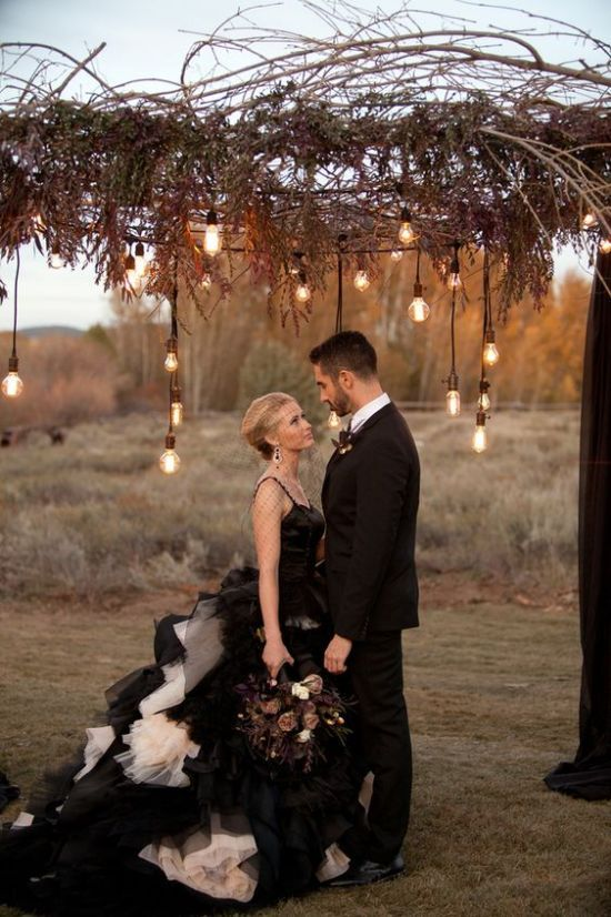 an industrial wedding arch decorated with black fabric, dried herbs and greenery, twigs and bulbs hanging down
