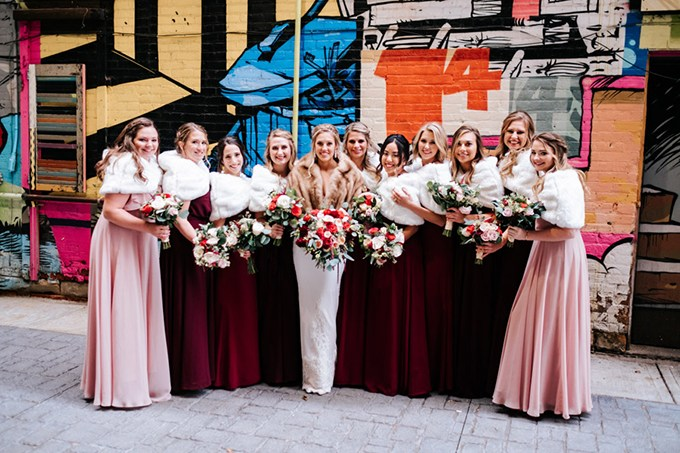The bridesmaids were wearing burgundy and pink maxi gowns and white fur wraps