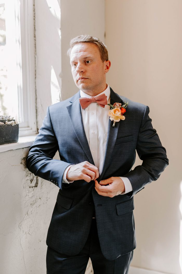 The groom was wearing a blue suit, a coral bow tie and a matching boutonniere